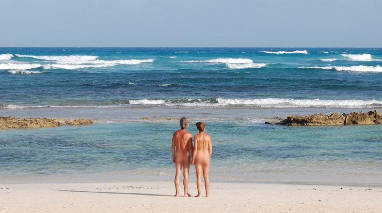 Hombre y mujer nudistas frente al oceano