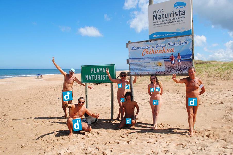 Nudistas en la playa posando para una foto