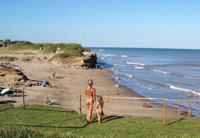 Madre e hija desnudas observan playa