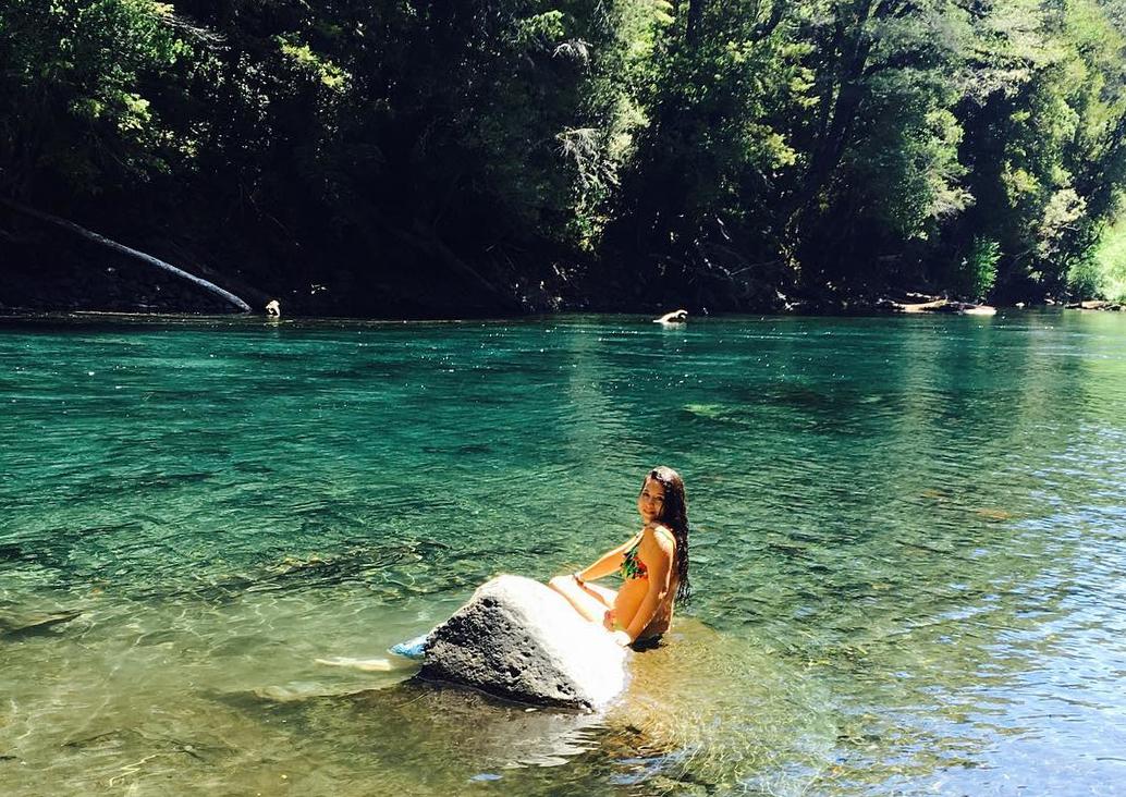 Mujer bañandose a la orilla del río