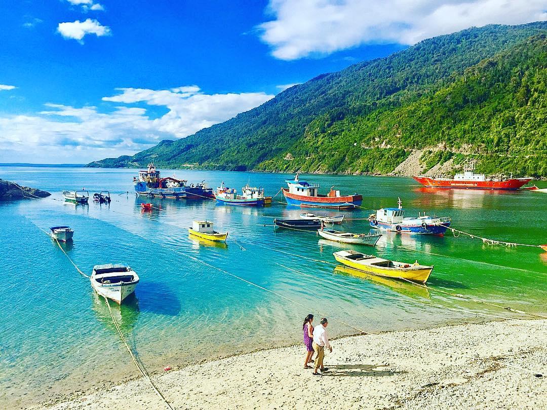 Barcos y personas en la orilla de una caleta
