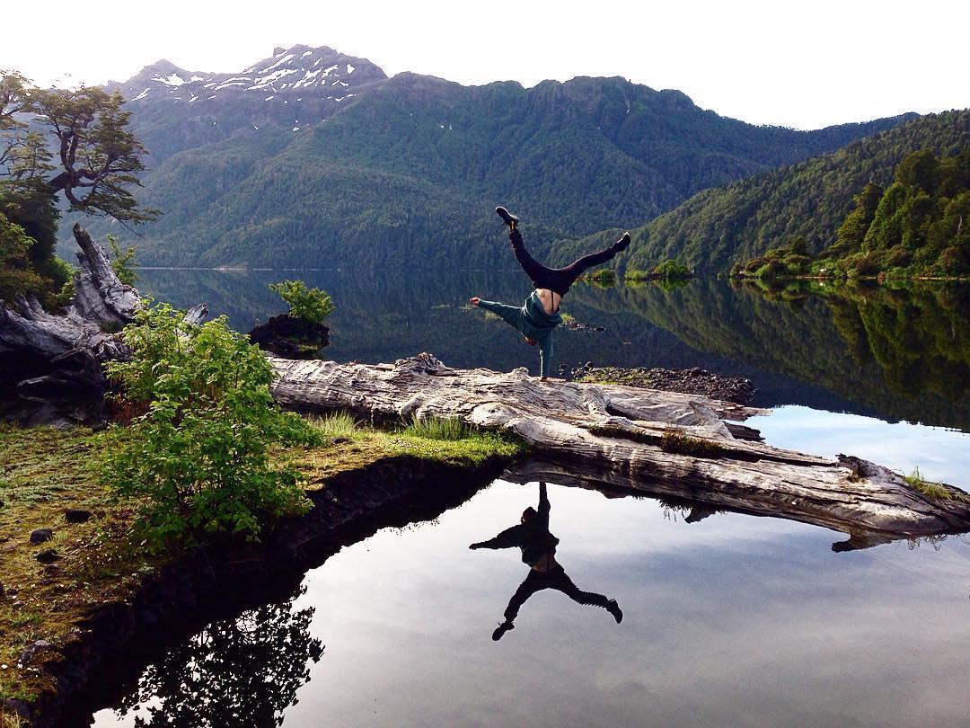 Hombre parado en sus brazos frente a lago