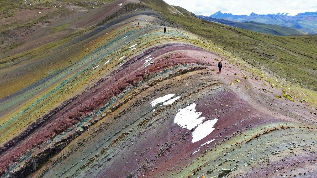 Viajeros caminando por montaña de colores Palcoyo