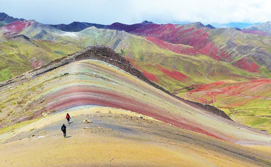 Dos viajeros caminando por montaña de colores Palcoyo