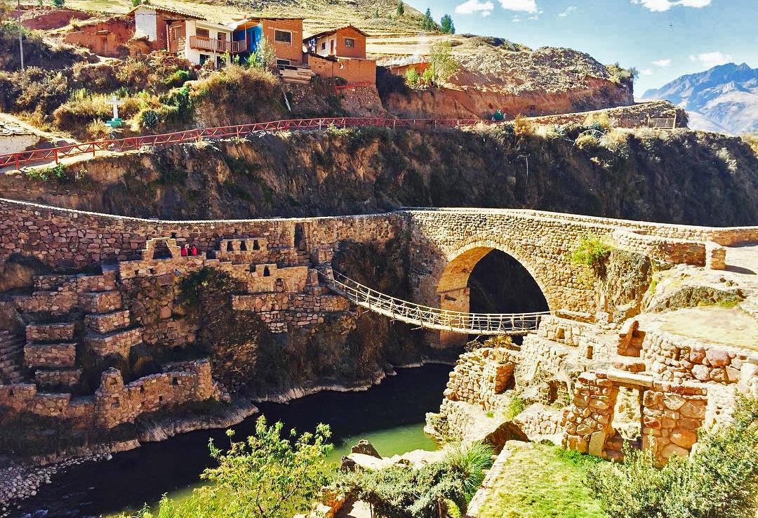 Puente colgante y de piedra frente a casas
