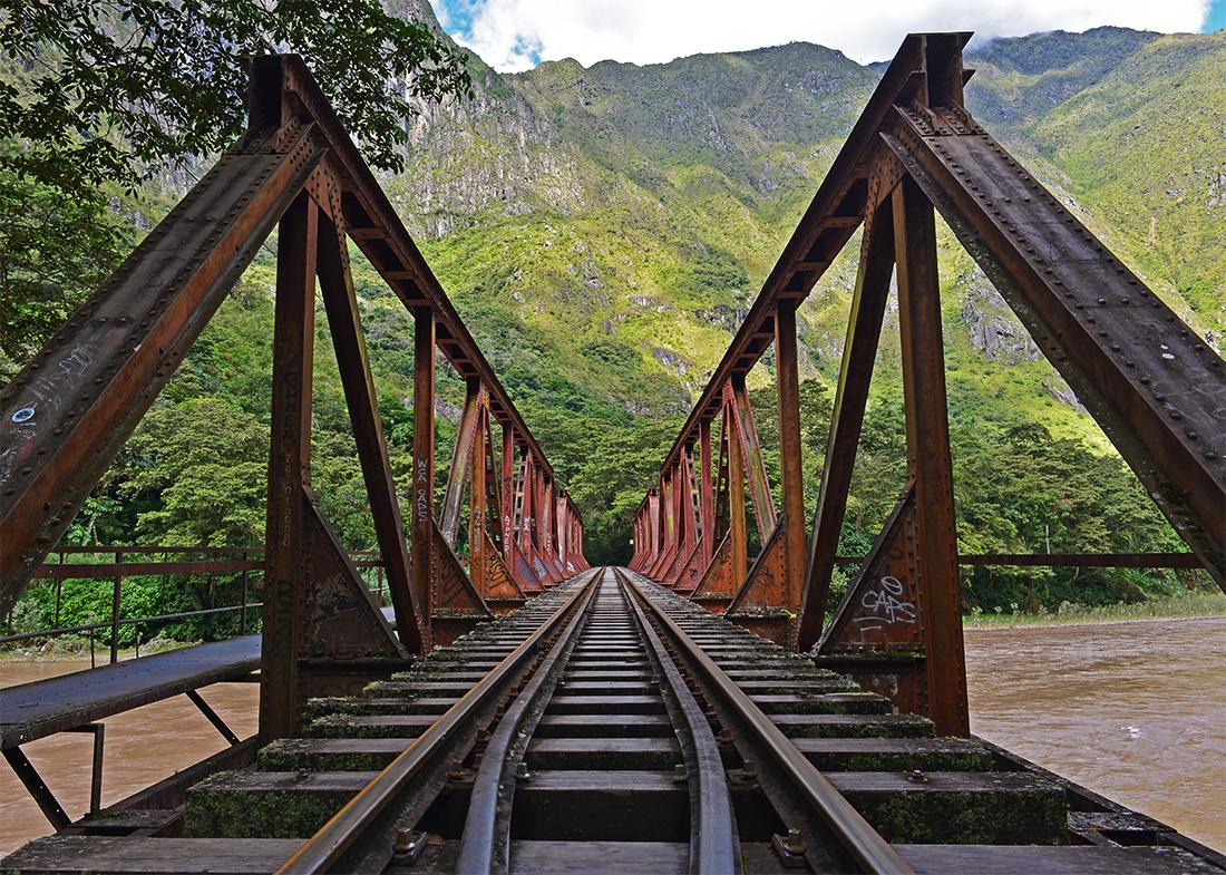 Puente para tren sobre río en medio de selva peruana