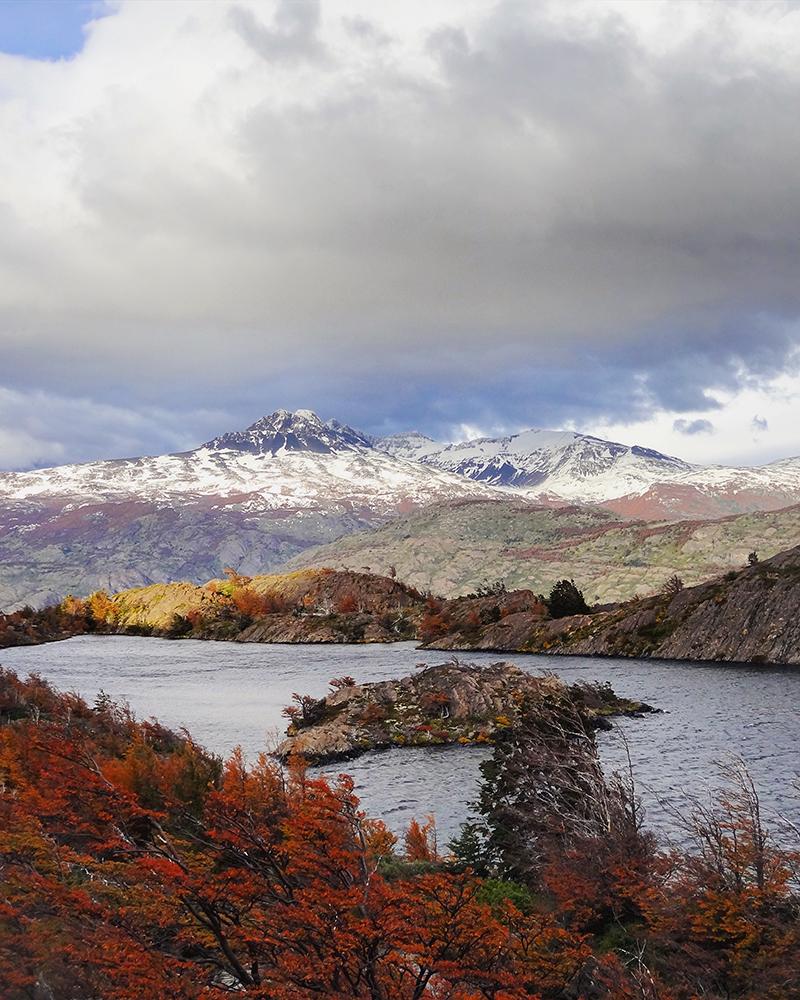 Lago, montañas, nubes y arboles rojos