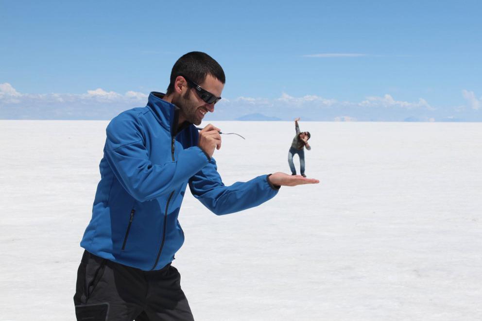 Dos viajeros jugando con efectos de perspectiva en el Salar de Uyuni