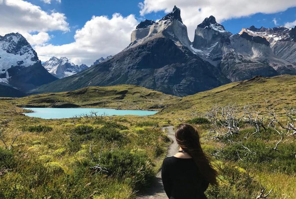 Viajera observando laguna color calipso y paisaje montañoso de fondo en Torres del Paine