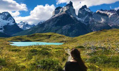 Mujer viajera frente a lago y torres montañosas
