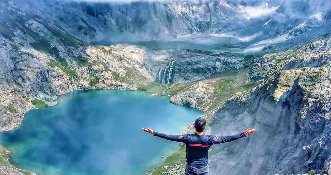 Hombre extendiendo brazos frente a lagunas y montañas