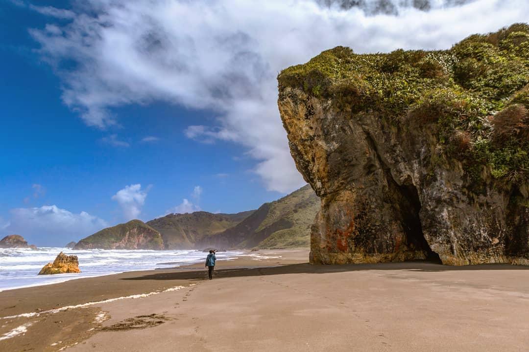 Persona caminando en la playa junto a roca gigante