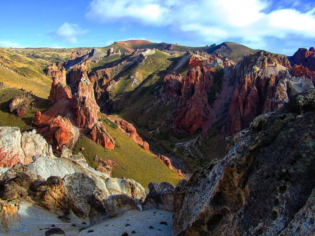Montañas verdes con gigantes rocas rojas