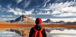 Joven parado frente a laguna y montañas
