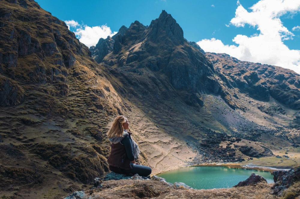 Mujer sentada frente a montaña y laguna esmeralda