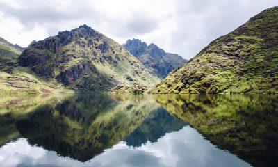 Montañas verdes reflejadas en laguna