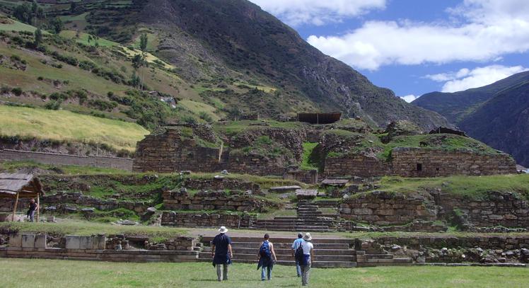 Tres viajeros caminando hacia restos arqueológicos