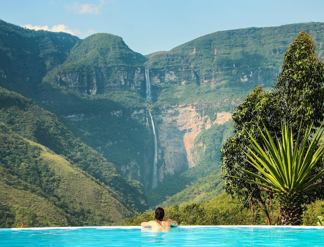Mujer en piscina frente a catarata
