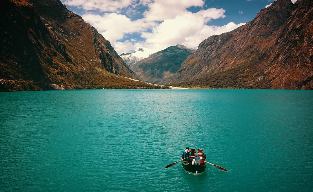Momentos románticos frente a laguna turquesa y personas en bote