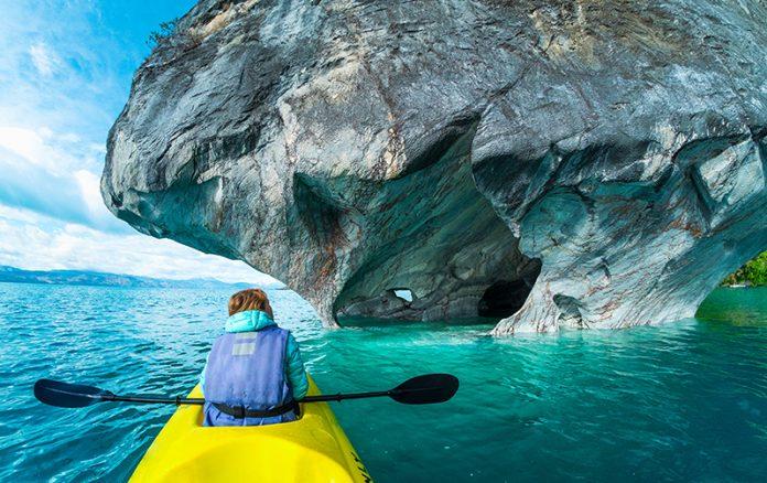 mujer navegando en kayak por lago celeste