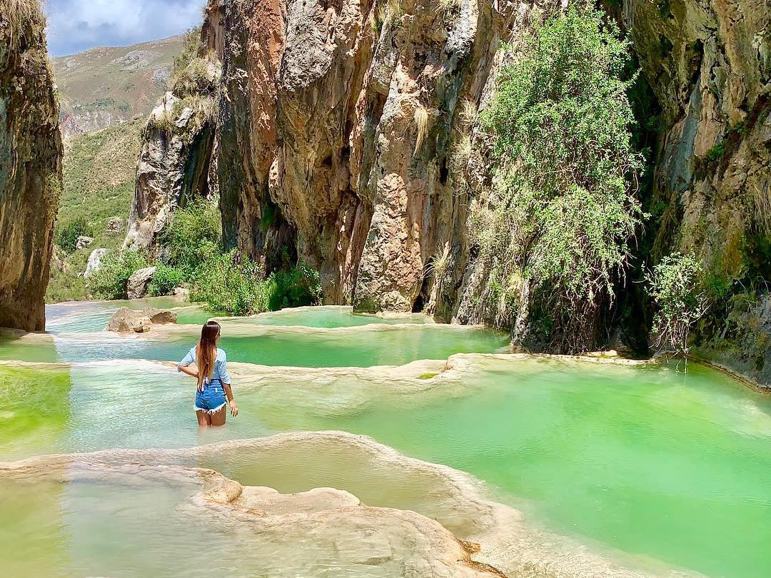 Chica sobre piscinas naturales de color esmeralda en Ayacucho