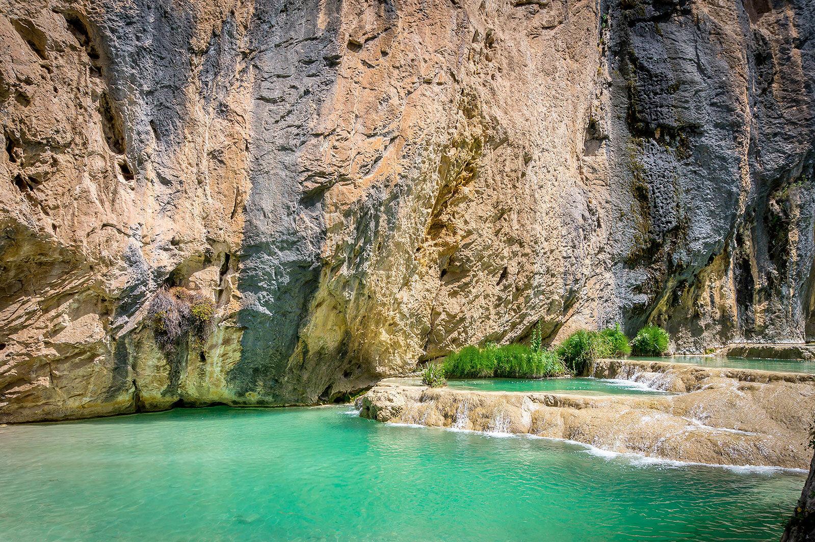 Piscinas color esmeralda y muro de rocas de fondo