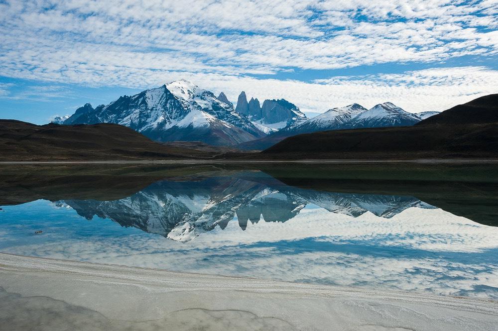 Laguna que refleja montañas al fondo
