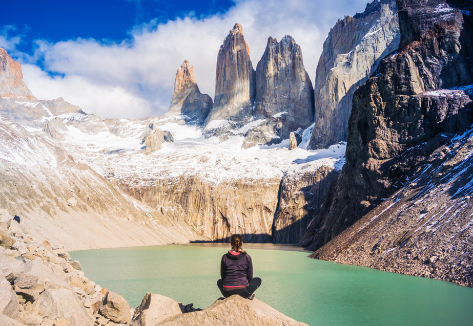 Persona sentada sobre roca observando laguna y paisaje montañoso en Base Torres