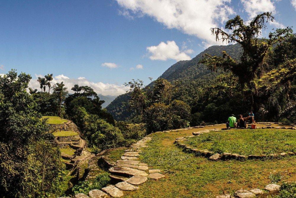 Grupo de viajeros descansa frente a ruinas arqueológicas de la Ciudad Perdida