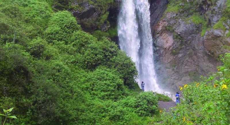 Viajeros frente a gran catarata en trekking en lima