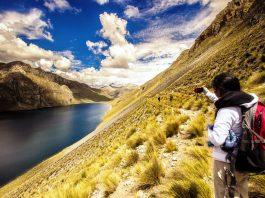 Joven tomando fotografía en paisaje de trekking desde Lima
