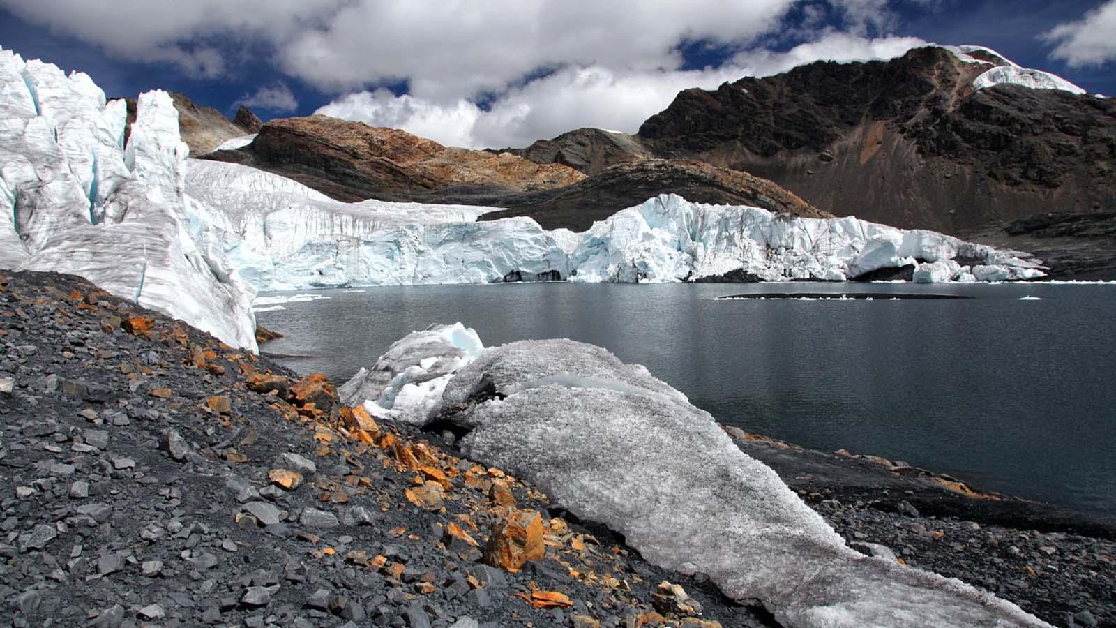 Glaciar frente a laguna y bajo cielo semi despejado