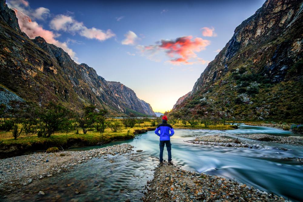 Viajero observa paisaje montañoso en trekking Santa Cruz