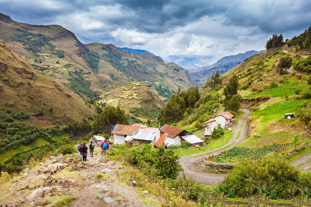 Viajeros caminan por paisaje agrícola en trekking santa cruz