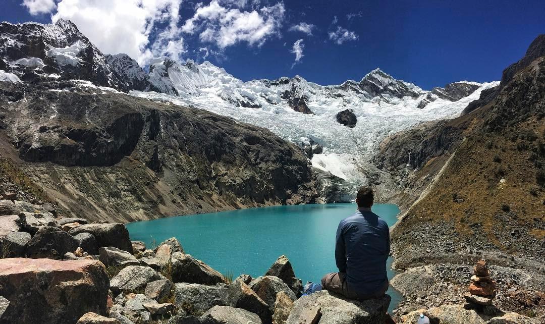 Viajero observando montañas y laguna color turquesa