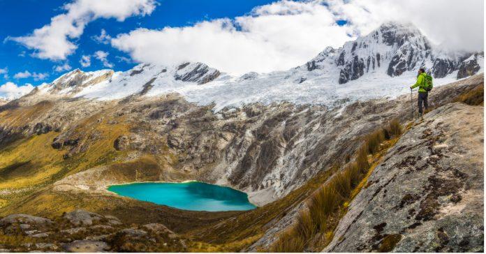 Viajero observa laguna y paisaje montañoso