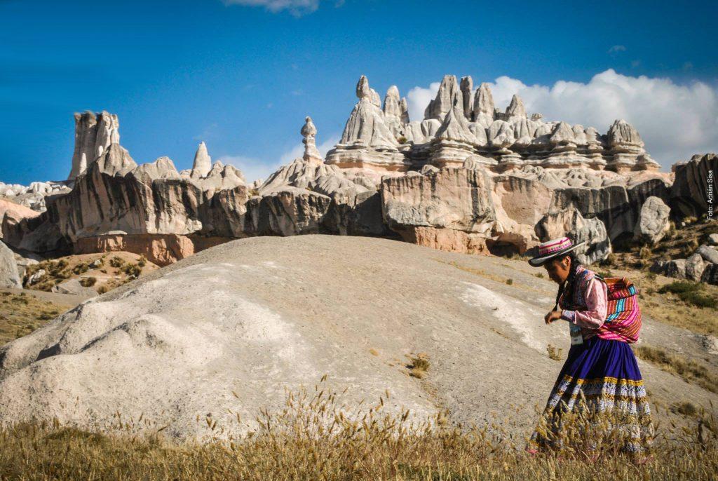 Mujer caminando frente a bosque de piedras