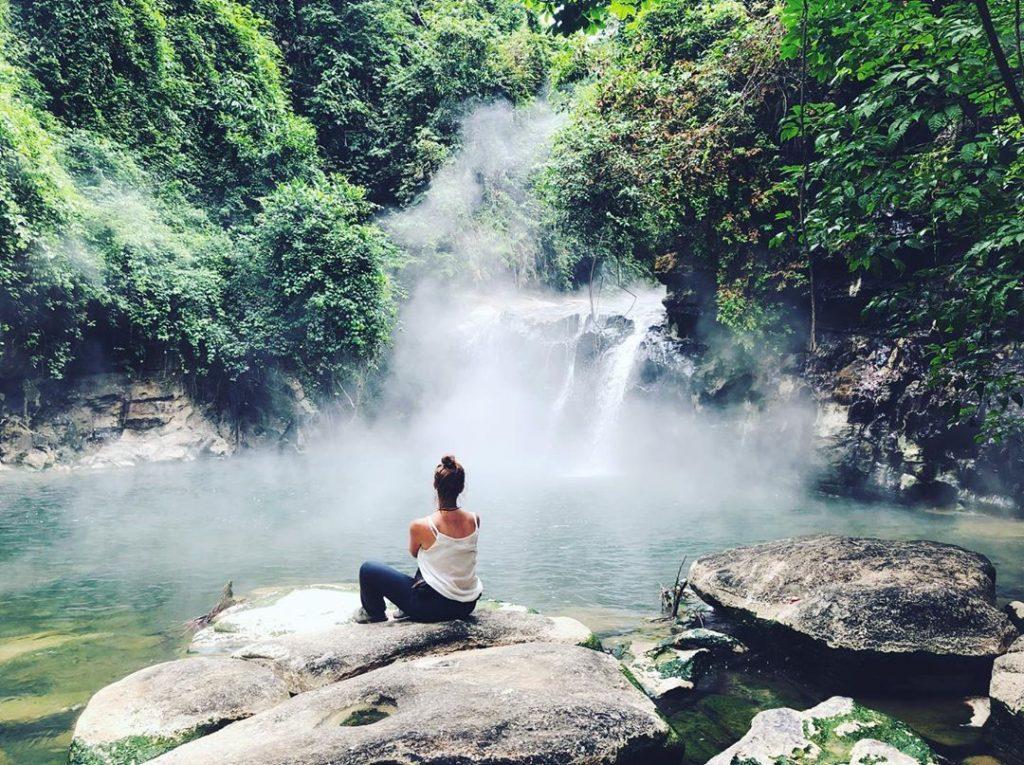 Viajera sentada frente a pequeña caída de agua de río hirviente