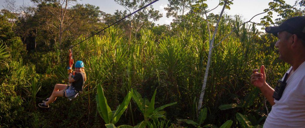 Niña realizando canopy en la selva