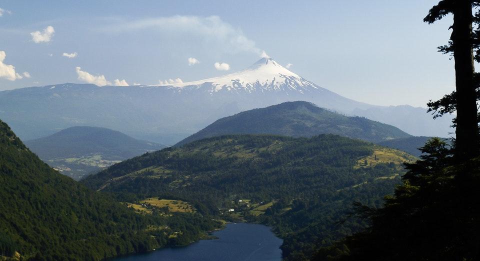 Volcán humeante frente a laguna