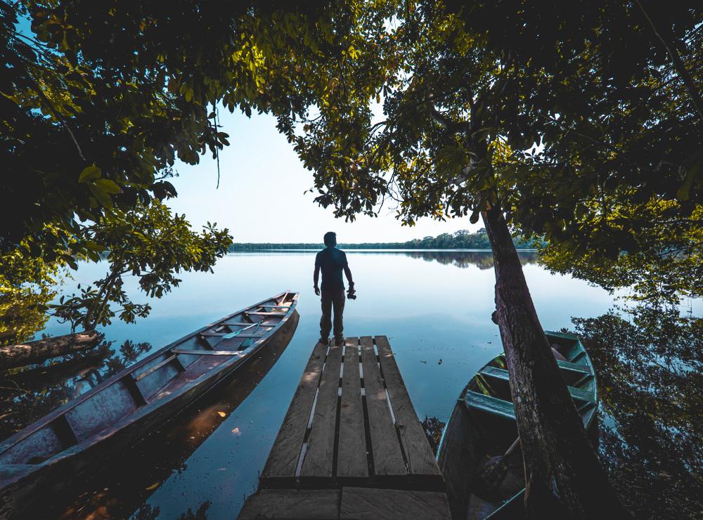 Hombre observa un lago amazónico