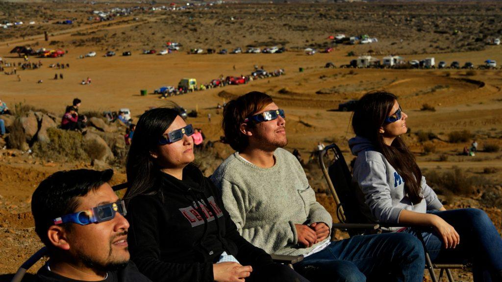 Amigos observando eclipse solar total con lentes especiales