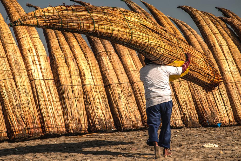 Hombre transportando caballito de totora