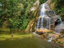 Hombre bañandose frente a cascada en la selva