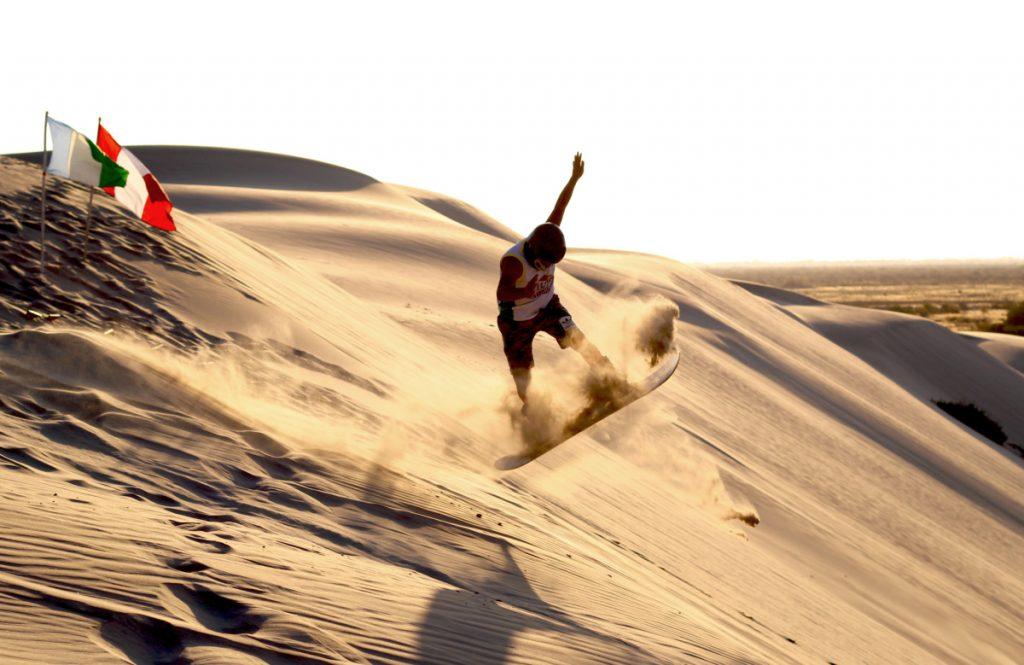 Hombre haciendo sandboard en dunas de piura