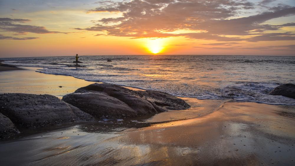 Playa con un pescador en el atardecer