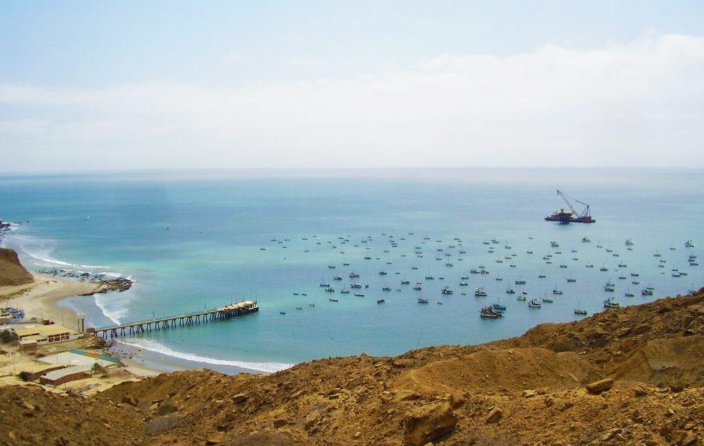 Playa con aguas cristalinas y botes de pescadores