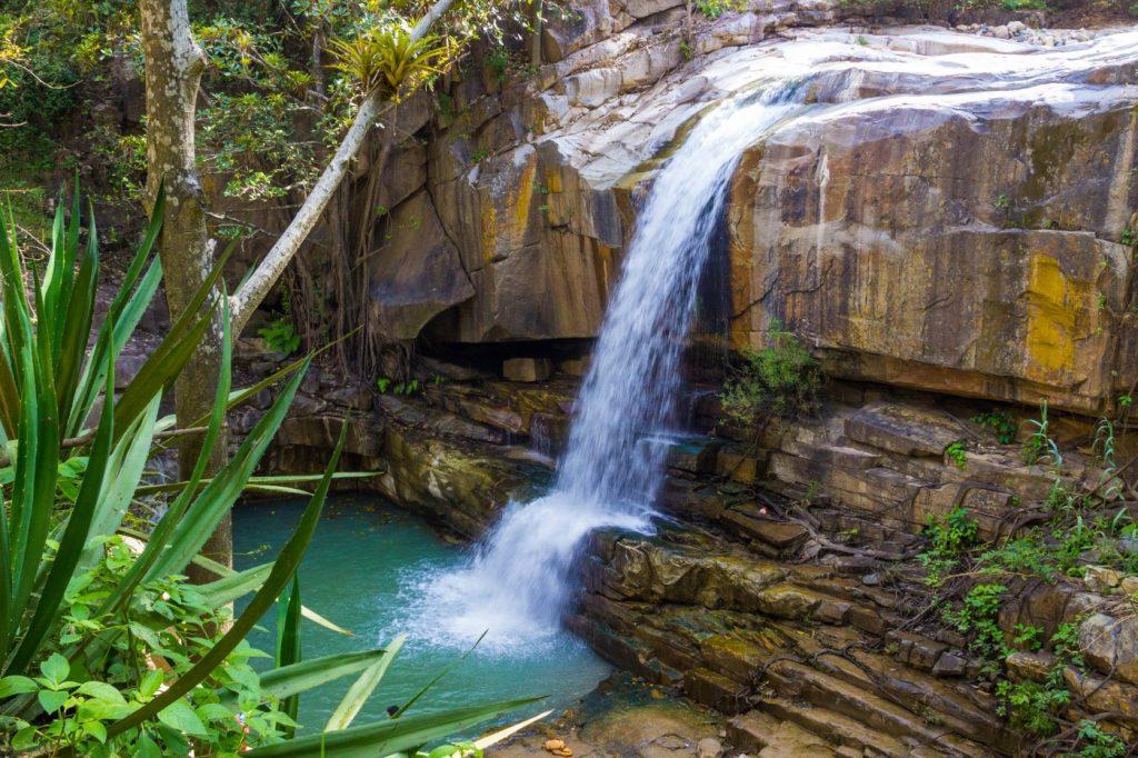 Catarata sobre rocas y piscina de agua turquesa