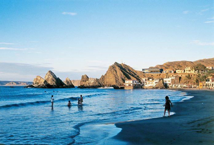 Personas bañándose en playa de Piura