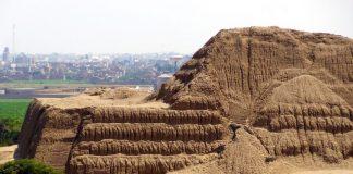 Viajero en moto frente a complejo arqueológico